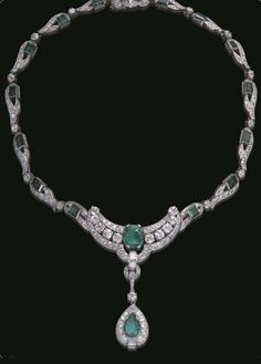 AN ART DECO EMERALD AND DIAMOND NECKLACE, CIRCA 1930. The detachable single and old European-cut diamond pendant, centring upon a pear-shaped emerald, enhanced at the base by a baguette-cut diamond arch, suspended by a series of single and baguette-cut diamond links, from a crescent-shaped old European-cut diamond openwork plaque, centring upon a cushion-cut emerald, mounted in white gold.