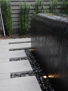 Curved infinity edge pool facing the living space. A great use of a black glass mosaic pool tile disappearing into a hidden balance tank. BASK Pool Design, Melbourne