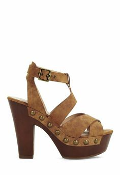 Strappy heel sandal with  adjustable ankle strap, big studding around the foot, and an open back counter. Wood-like sole and stacked heel. Nubuck leather.