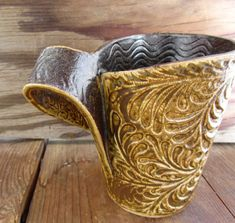 This unique stoneware mug is created from one slab of clay that has been wrapped to form a mug. Approximate size: 5 tall, 4 top opening, 2 1/2 bottom diameter, handle is 1 1/2 at its widest and sticks out from mug about 2 - holds 10 ounces of liquid    **All glazes are non-toxic and food safe**    *dishwasher safe