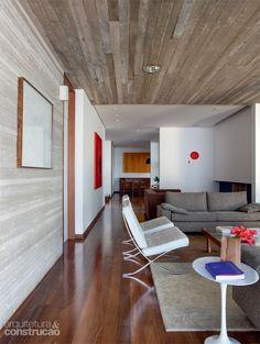 Em contraste com as paredes frias, o chão de toda a casa, inclusive dos quartos, recebeu réguas de cumaru de 10 cm de largura.