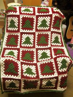 This is a beautiful Christmas tree afghan made in a granny square design. A beautiful afghan for yourself or to give as a gift for the holidays. This is a hand crocheted lap afghan. It is perfect to have on the back of your chair to pull off and use whenever. It is made in a pet-free, smoke-free environment. It is approximately 57 x 38.  **Please remember that computer monitors show colors differently, so the actual color of the item may be a little different from what you see on your…