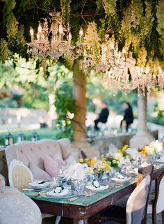 Chandeliers, wooden tables and lounge chairs #tablescape #wedding