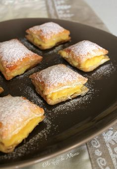 "The ""sporcamuss"" are the squares of puff pastry filled with custard and covered with a dusting of powdered sugar. Special features of these sweets is that go strictly served hot, almost boiling, both in winter and in summer and eating them inevitably you get dirty ""u muss"" that in our dialect means ""mouth"".  http://www.polignanomadeinlove.com #vieniamangiareinpuglia #italianfood #sweet #madeinitaly"