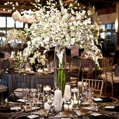 Centerpieces of varying heights were placed at alternating tables. The vases were clear, black, or white and all were filled with white flowers. Surrounding votive candles added a romantic touch.