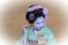 April 2015: maiko Hisamomo of Pontocho with custom cherry blossom kanzashi and high okobo shoes.