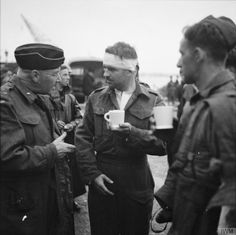 Captain Jock Anderson of the Royal Regiment of Canada, cup of tea in hand, recounts his experiences to Brigadier Tees after disembarking at Portsmouth. THE DIEPPE RAID, 19 AUGUST 1942.