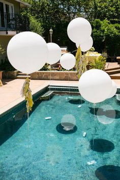 Create this whimsical display by tying weights to the end of your balloon strings + positioning them throughout the pool.