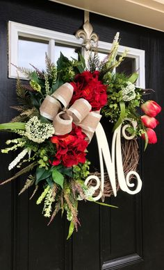 New item!! This gorgeous door wreath is ready to grace your front door! Made up on a 18 grapevine wreath with moss, mixed greens of ferns, maple leaves, and ficus leaves. Gorgeous spring red hydrangeas, tulips and white accents make up this beautiful door wreath. A decorative cream satin w/ burlap bow and a 12 Ivory script monogram make this wreath so pretty and one of kind. Measures approx: 30 x 25 X 7 (tip tip tip). I truly love what I do and I take each wreath personally. I always...