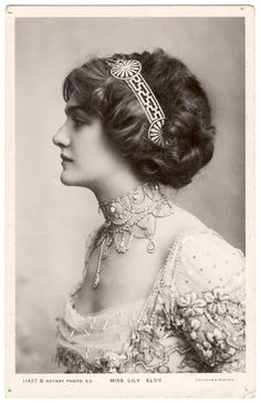 This is Lily Elsie , one of the most popular actresses in this period . She got curly short hair , wore a open-neck dress . Perhap ,people in this time prefered plump body than skinny body