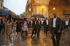 President Barack Obama steps over a puddle as he and his family tours the cobbled streets ...