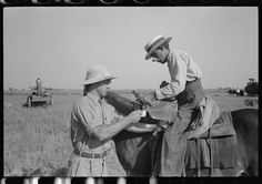 Rice farmer getting drink of water from water boy on farm near Crowley, Louisiana Photographer Russell Lee September 1938