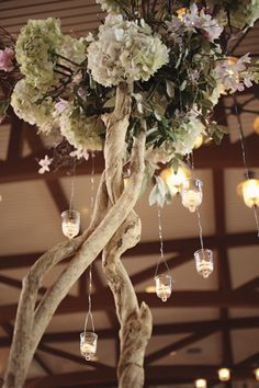 To accommodate the dining room's tall ceilings, The Place for Flowers designed breathtaking branch centerpieces topped with mounded floral arrangements of pink hydrangeas, peonies, roses, and orchids and small hanging tea lights.