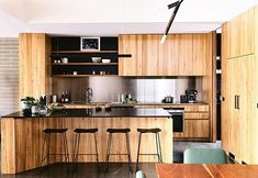 A Melbourne couple called on some architectural expertise to create a contemporary family home. Can you tell by this awe-inspiring kitchen space? A stainless-steel splashback contrasts with warm messmate cabinetry by Cleverdon Cabinets and Zimbabwe granite benchtop, and 'Winnie' sttols from @husetshop transform the island bench into the perfect eat-in space for a busy family. See more via the link in bio. Photos by @derek_swalwell. Styling by @rachelvigorstylist.⠀