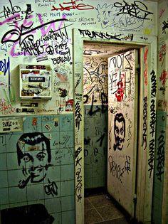 Gritty graffiti riddled bathroom.