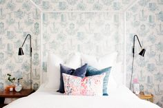 Blue and white wallpaper in eclectic bedroom with colorful pillows