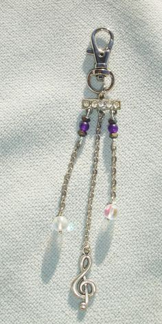 """This fashion charm features a clasp to attach it to about anything! Features a vintage rhinestone finding, gemstone beads, and a music note charm! Measures 4.75"""" long. Makes a great gift!"""