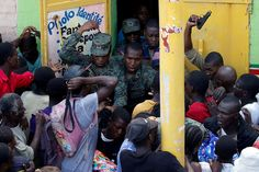 20161024 - Haitian soldiers shoot in the air to try to control the crowd as they wait for food to be handed out after Hurricane Matthew hit Jeremie, Haiti. #  Carlos Garcia Rawlins / Reuters