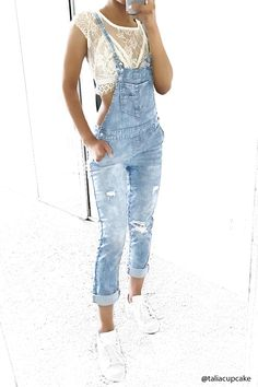 A pair of denim woven overalls with distressing on the legs, a four-pocket construction, buttons on each side, a bib patch pocket, and self-tie adjustable straps.