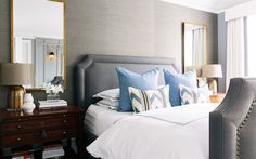 Love the different shades of grey on the headboard & wallpaper & the brass/bronze metal accents.