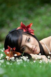 девушка с цветами в волосах лежит на траве