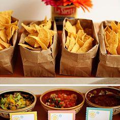 Un bar à tacos—On prépare des petits sachets de croustilles de maïs que nos invités pourront tremper dans un guacamole ou une salsa maison. À leurs côtés, on dispose une pile de tortillas de maïs et tout ce qu'il faut pour garnir nos tacos: bœuf haché aux épices chili, porc effiloché, poisson croustillant, tofu mariné, chou rouge, poivrons, radis, maïs, coriandre, crème sure, lime... Il ne manque q...