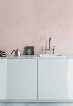 Cozinha com parede rosa millennial, armários brancos e bancada de pedra granito itaunas.