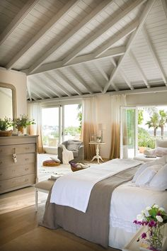 Gorgeous country bedroom with white and neutral bedding, shiplap ceiling and exposed beams.