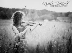 senior girl pose with violin and flower field