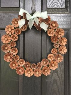 This wreath is handmade out of Pinecones. Pinecones are cut into flower shape and left natural to give it a rustic look. The Base is, 12in however finished wreath is about 18in. Bow is tied on and can be easily adjusted if you prefer bow in a different position on the wreath.