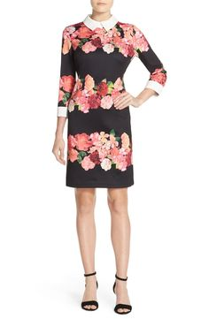 Polished with a crisp collar and cuffs, this smooth, stretchy scuba dress from Vince Camuto bursts with color in bunched blooms that contrast the black backdrop.