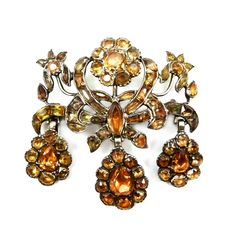 18th century golden topaz triple drop cluster brooch, Iberian c.1760   , designed as a crossed triple scroll stems supporting three graduated flowerheads, suspending three pear shaped cluster drops, close set in silver   Length 5.5cms