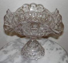 """Priscilla footed Compote, made by Dalzel, Gilmore, and Leighton when they were located in Findlay, Ohio beginning 1888.  The pattern is called """"Priscilla"""" also known as """"Alexis"""", and """"Sun and Star"""", the company called it """"Crown Jewel"""". 7""""H x 8.5""""D. Note:  L.G. Wright did reproduce this compote in the 1970's.  In their catelogs it clear that they never made it in this original shape."""