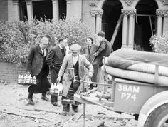 Milkmen deliver the morning round along a rubble strewn street, as householders discuss the damage to their properties following a V-1 attack in Upper Norwood, 1944. A vicar can also be seen walking along the street. The front doors and all windows are missing from these homes, and the interiors appear as shells, with a few timbers or a ladder all that is visible inside.