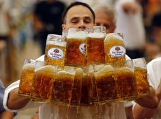 German Oliver Struempfl competes to set a new world record in carrying one liter beer mugs over a distance of 40 m (131 ft 3 in) in Abensberg September 7, 2014. Struempfl carried 27 mugs over 40 meters to set a new record for the Guinness book of records. (REUTERS/Michael Dalder)
