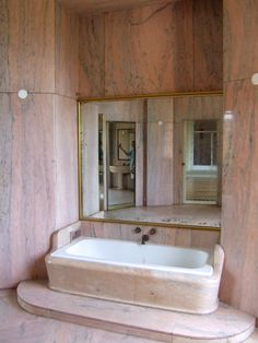 [If you look closely at the marble, you can see yellow or warm tan in it, along with with blue-grey. Or in other words, gold and silver tones to go with the pink. Very posh. I like the use of the big mirror to brighten up the alcove. The platform and tub surround are very cool, as are the angled walls (like a book cover being opened). If I were an architect, I'd make a cardboard model of this like those books you open and a 3D scene folds out. Good sales tool!] casa de banho,Fundaçao…