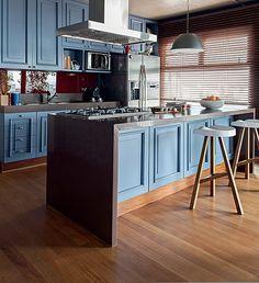 A cozinha projetada pelo arquiteto Nelson Kabarite é composta por armários de madeira com inspiração londrina. O mesmo desenho do móvel aparece na ilha central, que acomoda o cooktop e ampla bancada para preparo das refeições