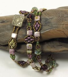 A triple wrap bracelet using SuperDuos and Czechmate Tiles in tones of olive and amethyst. The Czechmate Tiles are luster opaque gold/smoky topaz which are a pale amethyst color splashed with topaz swirls and pale green undertones. These colors blend extremely well together. The SuperDuos are ultra luster opaque green and metallic purple and accent the tiles beautifully. Czech fire polished beads in amethyst and olivine have been interspersed. The seed beads are Toho antique bronze which tie…