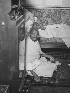 Mahatma Gandhi spinning in his cabin on board ship. Sir P Pattani, prime minister of Bharnagar, rests beside him. (Photo by Miller/Topical Press Agency/Getty Images)