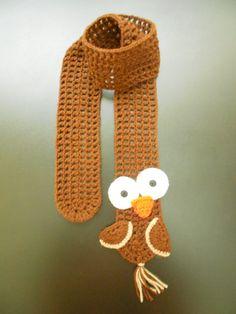 CACHECOL PÁSSARO MARROM: em crochê com lã 100% acrílica.  Marrom, com aplicações de crochê em motivo de pássaro em uma das extremidades.  Se desejar, solicite na cor de preferência da criança.  Básico e divertido!  Comprimento: 120 cm. R$ 50,00.