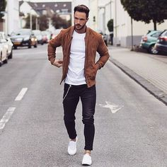 Try teaming a cognac suede bomber jacket with black jeans for a casual level of dress. Tap into some David Gandy dapperness and complete your look with white low top sneakers. Shop this look on Lookastic: lookastic.com/... — Tobacco Suede Bomber Jacket — White Crew-neck T-shirt — Black Jeans — White Low Top Sneakers