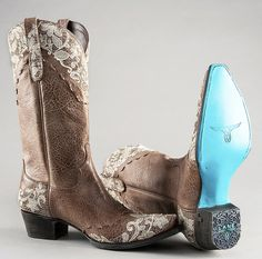 """Jeni Lace handmade in Mexico by Lane Boots Texas. Intertwined lace around the uppers and across the vamps is subtle and gentle.  Delicate floral pale yellow embroidery provides the finishing touch. A shock absorbing antibacterial moisture wicking memory foam footbed awaits you, designed for all day comfort. Only the highest quality full-grain cowhide and kid skins are used. She stands 15"""" tall with 1-3/4"""" cowboy heels, a """"snip toe"""" design and Lane's trademark Turquoise outer soles."""