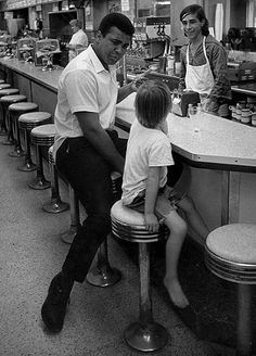Muhammad Ali with young fan in a diner 1970