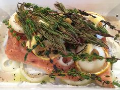 Delicious herbed up salmon. I baked it with sliced onion and lemon, fresh oregano, rosemary, and thyme, then drizzled with olive oil and a sprinkling of salt and pepper. The onions, lemon, and herbs really permeate the salmon.