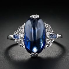 This unusual Art Deco sapphire and diamond ring showcases a vivid blue elongated oval cabochon cut sapphire weighing 3.45 carats. It is flanked on each side by three twinkling rose cut diamonds and three square calibre cut sapphires. The stunning center sapphire is completed with a rose cut diamond set at each end. A bold, yet d