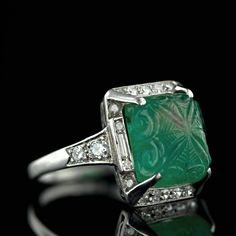 The Art Deco period is renowned for its beautifully carved gemstones, and this ring is no exception. Carved with scrolls and an intricate web pattern, the 6 carat lozenge shaped emerald cabochon glows from within a platinum framing of baguette and single-cut diamonds. This original 1920's gem is finished with a scroll work gallery and old European-cut diamond shoulders.