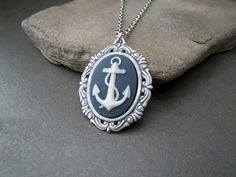 A pretty navy and white resin cameo has been set into a hand made oxidized silver Victorian setting. The pendant suspends from an oxidized silver brass link chain with a matching clasp. Your necklace