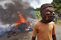 A protester opposed to the Burundian President's third term wears a mask near a burning barricade in the Kinama neighborhood of Bujumbura on May 25, 2015.