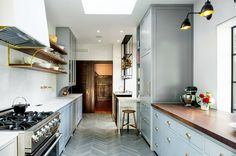 Long galley style kitchen with gray herringbone tile floor & brass shelving