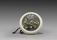 ANTIQUE CLOISONNÉ & IVORY MANJU NETSUKE Rare and antique, ivory and cloisonné enamel kagamibuta manju netsuke; the plate with scrolling lotus design set into a finely polished ivory bowl; unsigned, 19th Century